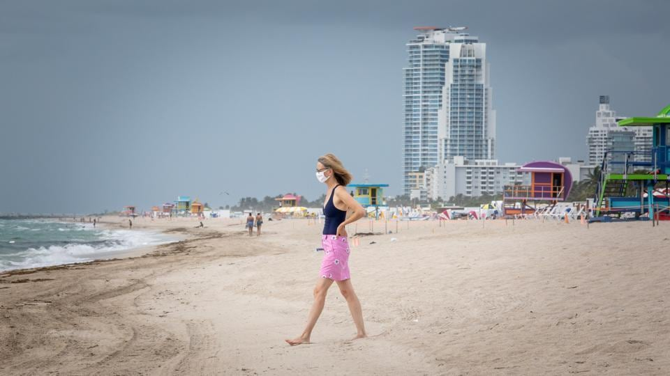 A woman wearing a face mask walks towards the water at a beach in Miami, US on July 17. The United States, with more than 3.6 million confirmed cases as of July 18, is still seeing huge daily jumps in its first wave of COVID-19 infections.  (Jayme Gershen / Bloomberg)