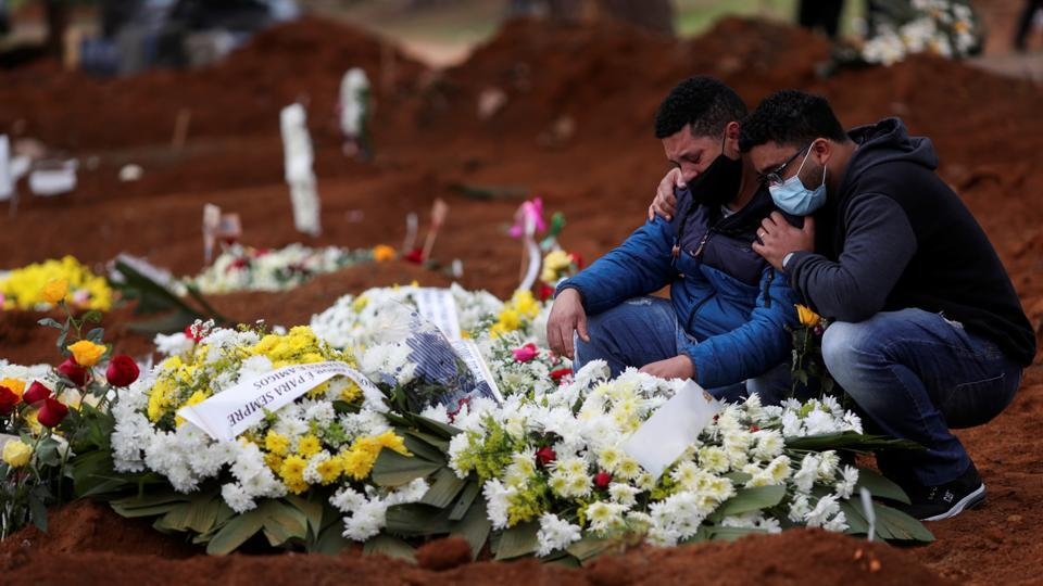 Relatives react near the grave of Neusa Freitas dos Santos, 81, who died from the coronavirus disease (COVID-19) after the burial at Vila Formosa cemetery, in Sao Paulo, Brazil on July 16. Brazil, the largest country in South America has passed 2 million confirmed cases of coronavirus infections and logged over 77,000 lives lost to the Covid-19 disease. (Amanda Perobelli / REUTERS)