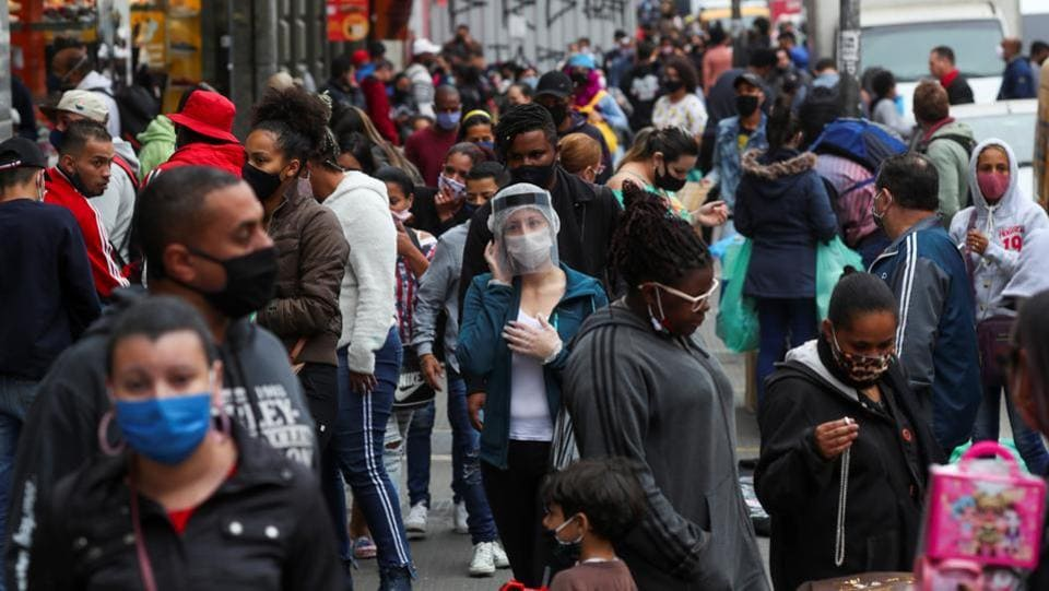 A woman wearing a face mask and a face shield speaks on the phone as people walk by at a popular shopping street in Sao Paulo, Brazil on July 15. In Brazil, the second worst hit nation after the US, more than 2 million people have tested positive including President Jair Bolsonaro, and more almost 78,000 people have died due to the virus. (Amanda Perobelli / REUTERS)