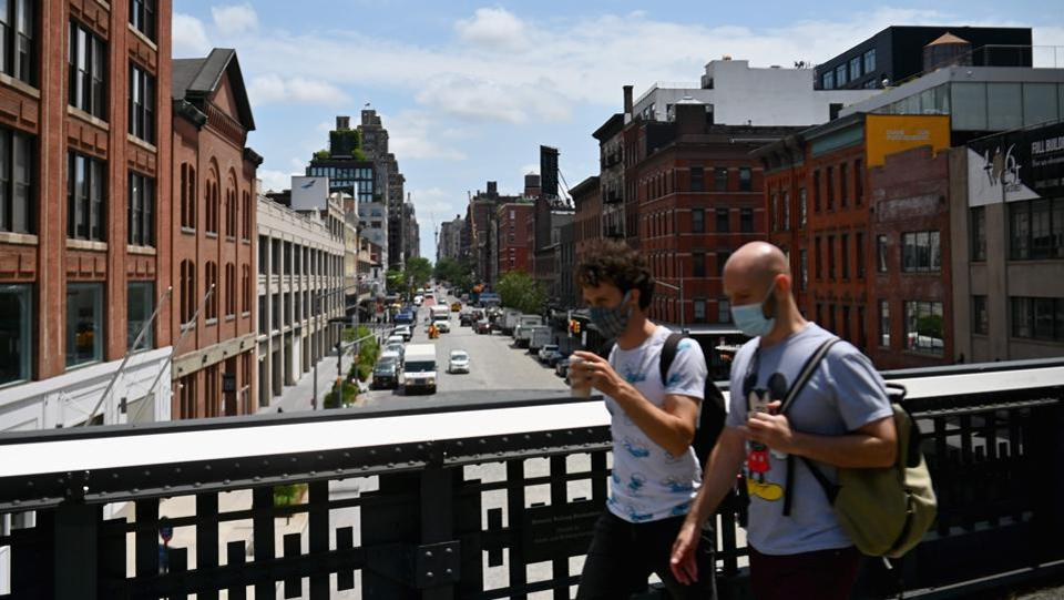 People take a walk on the High Line as it reopens to the public with limited capacity, in New York City, US on July 16. The United States reported two straight days of more than 70,000 new infections starting July 16, according to the Johns Hopkins coronavirus tracker. (Angela Weiss / AFP)