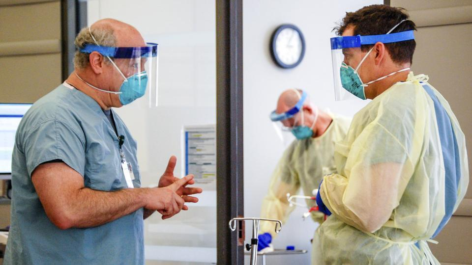Dr. Michael Saag, left, speaks with an unidentified coworker in Birmingham on July 10, 2020. Saag survived Covid-19 and now treats patients with the disease.