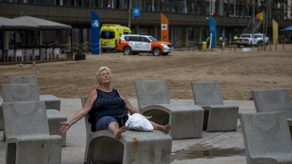 "A woman relaxes on a bench with her arms open near a beach in Barcelona, Spain on July 16. Many hard-hit countries have ""flattened the curve"" and are easing lockdowns while others, such as the cities of Barcelona and Melbourne, are implementing a second round of local shutdowns. (Emilio Morenatti / AP)"
