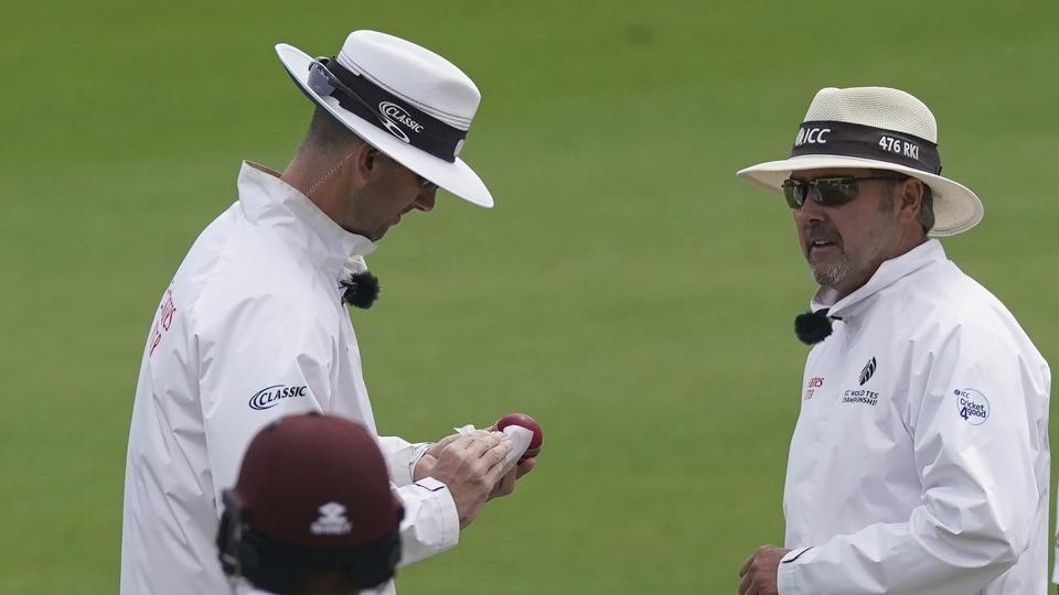 Umpire Richard Illingworth, right, watches as fellow umpire Michael Gough cleans the ball during the fourth day of the second cricket Test match between England and West Indies at Old Trafford in Manchester, England, Sunday, July 19, 2020. (AP Photo/Jon Super, Pool)