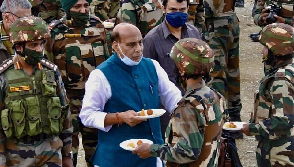 Defence Minister Rajnath Singh exchanges sweets while interacting with Indian Army personnel as he visits the forward posts near LoC in Kashmir on Saturday.