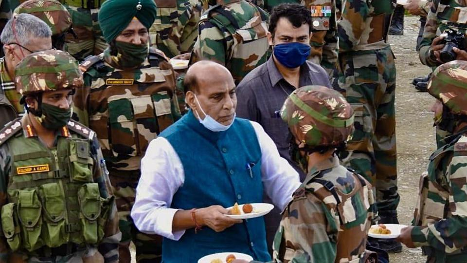 Defence Minister Rajnath Singh exchanges sweets while interacting with Indian Army personnel as he visits the forward posts near Line of Control, in Kashmir on Saturday.