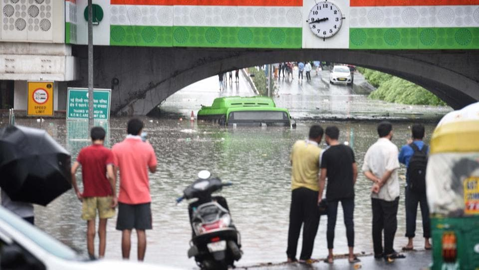 People look on at a DTC bus submerged after heavy rain and waterlogging under the Minto Bridge in New Delhi on July 19. The body of a 60-year-old man was found under the flooded bridge and according to Delhi Police officials, he drowned while trying to manoeuvre his vehicle through the waterlogged underpass. (Arvind Yadav / HT Photo)
