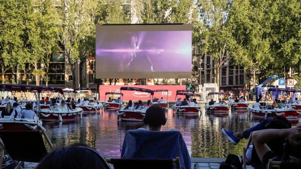 People watch the film Le Grand Bain seat on beach chairs and from boats at the Cinema on the water (Cinema sur l'eau) as a floating cinema with 38 socially-distant electric boats kicks off the Paris Plages summer event along the Bassin de la Villette, in Paris.