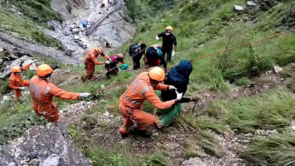 Teams of National Disaster Response Force (NDRF) and State Disaster Response Force (SDRF) rescue people near Pipalkoti in Chamoli on Monday,July 20, 2020 . They were stranded due to the closure of Badrinath National Highway owing to landslide.