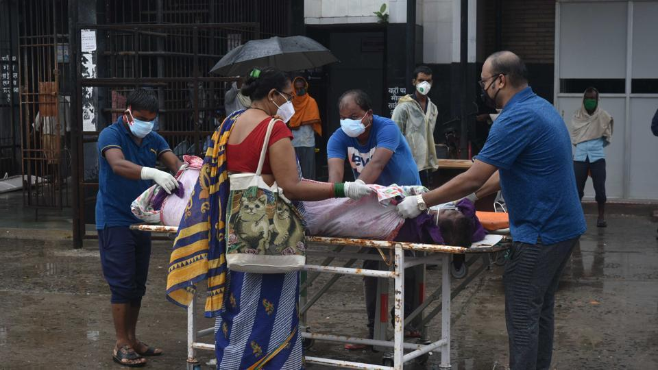 Family members of a coronavirus patient transport them by themselves to another hospital without proper gear after the hospital refused adequate attention at National Medical College and Hospital, in Patna on Monday.