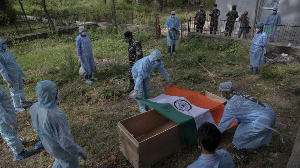 Indian paramilitary soldiers cover the coffin of their colleague who died of Covid-19, at a crematorium in Srinagar.