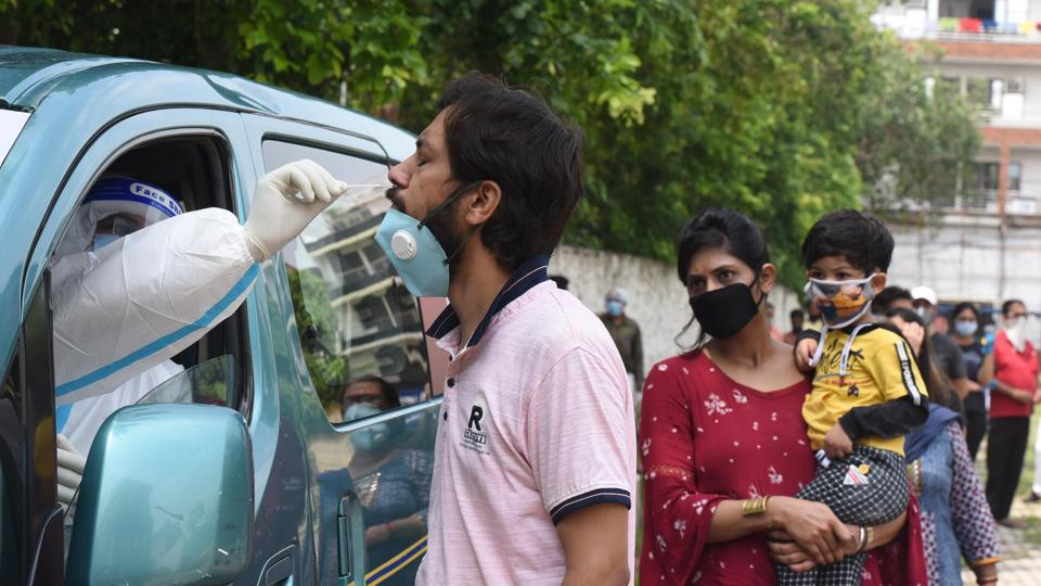 A health worker collects a swab sample from a man as others queue up for Covid-19 tests at Ramlila Maidan, New Delhi on July 21. According to the Union Health Ministry's data from a sero-prevalence survey released on July 20, as much as 23.48% of Delhi's population - 4.7 million people have been exposed to the virus that causes coronavirus (Covid-19) disease, HT reported. (Sonu Mehta / HT Photo)