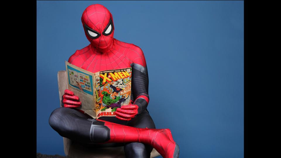 Evan Nuzum, dressed as Spider-Man, reads a comic book on day one of Comic-Con International in San Diego on July 18, 2019. (Rebecca Cabage/Invision/AP)