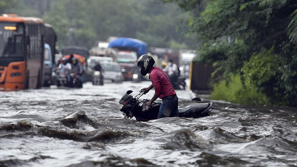 """A motorist pushes his vehicle along a waterlogged road near Indraprastha after a heavy downpour in New Delhi on July 22. Delhi once again recorded """"heavy"""" category rain after it poured in many parts of the city on July 22 morning. (Sanjeev Verma / HT Photo)"""