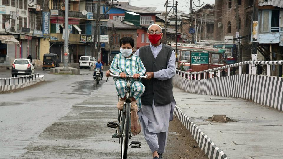 A man wearing face mask pulls his bicycle on a deserted road in Srinagar on Tuesday.