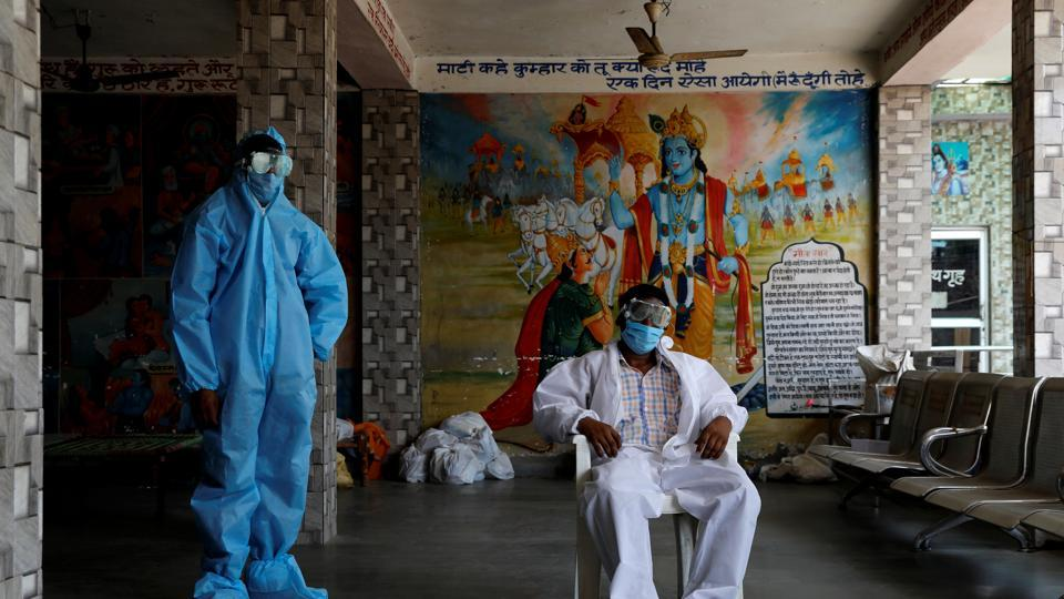 A priest and a labourer wear personal protective equipment (PPE) at a crematorium, amid the spread of the coronavirus disease (COVID-19), in New Delhi.