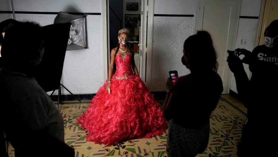 Naomi Ramos poses as she tries dresses for her quinceanera (coming of age of 15-year-olds) celebration amid coronavirus disease (Covid-19) spread concerns, in Havana, Cuba. (REUTERS/Alexandre Meneghini)