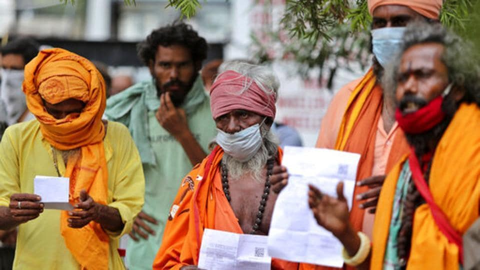 Hindu holy men wearing face masks wait to consult doctors at a Covid-19 screening facility inside a government hospital in Jammu, India, Tuesday, July 21, 2020.