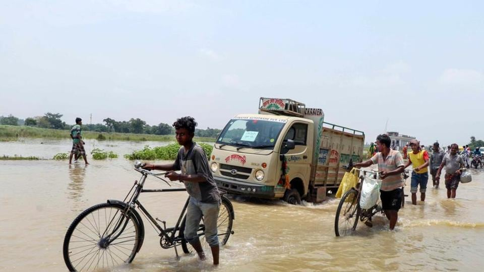 Commuters move through the floodwater of Kunye river following heavy monsoon rain, at Laghata in Birbhum district.