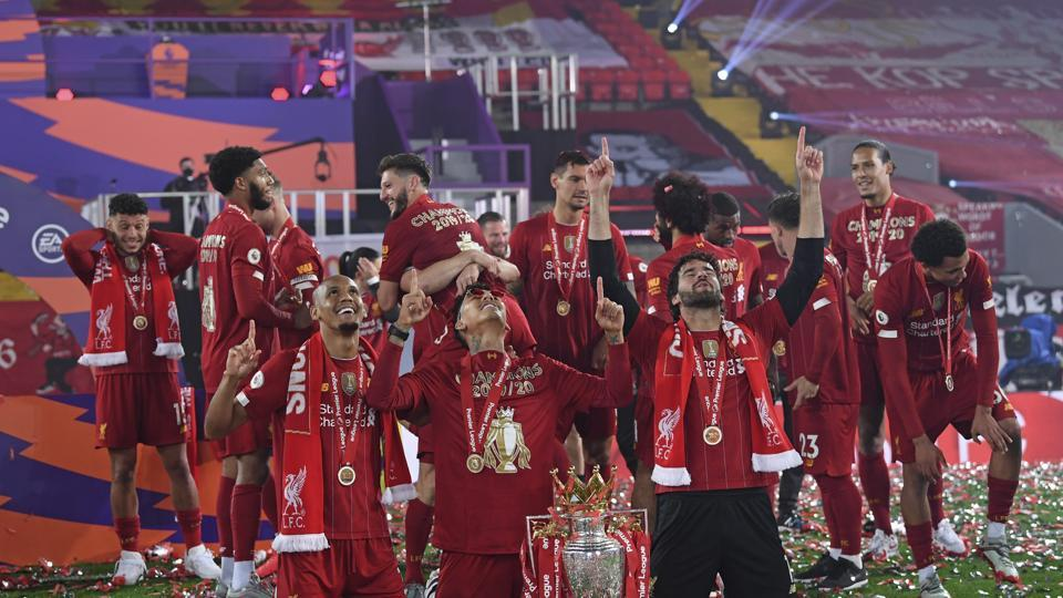 Liverpool's Fabinho, left, Liverpool's goalkeeper Alisson, right, and Roberto Firmino, all from Brazil, celebrate with the English Premier League trophy following the English Premier League soccer match between Liverpool and Chelsea at Anfield Stadium in Liverpool, England, Wednesday, July 22, 2020. Liverpool are champions of the EPL for the season 2019-2020. The trophy is presented at the teams last home game of the season. Liverpool won the match against Chelsea 5-3. (Laurence Griffiths, Pool via AP)