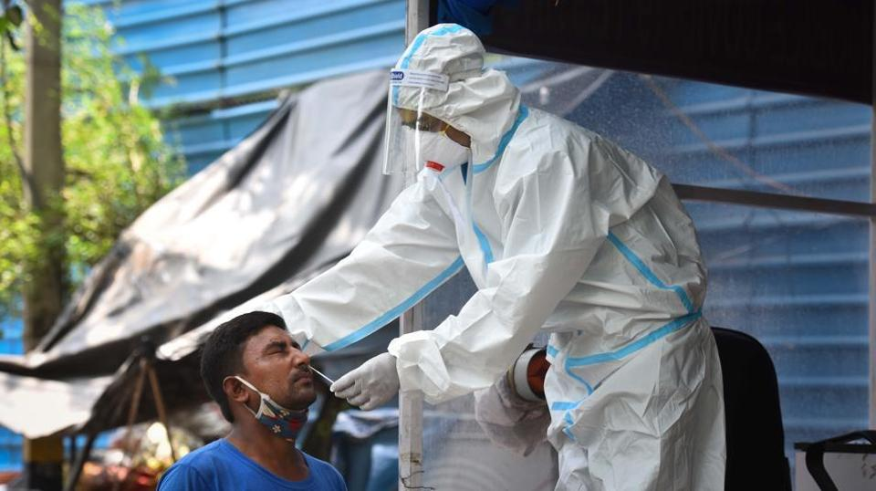 A health worker wearing PPE coveralls collects swab samples to test for coronavirus infection,  in New Delhi, on Tuesday, July 21, 2020.