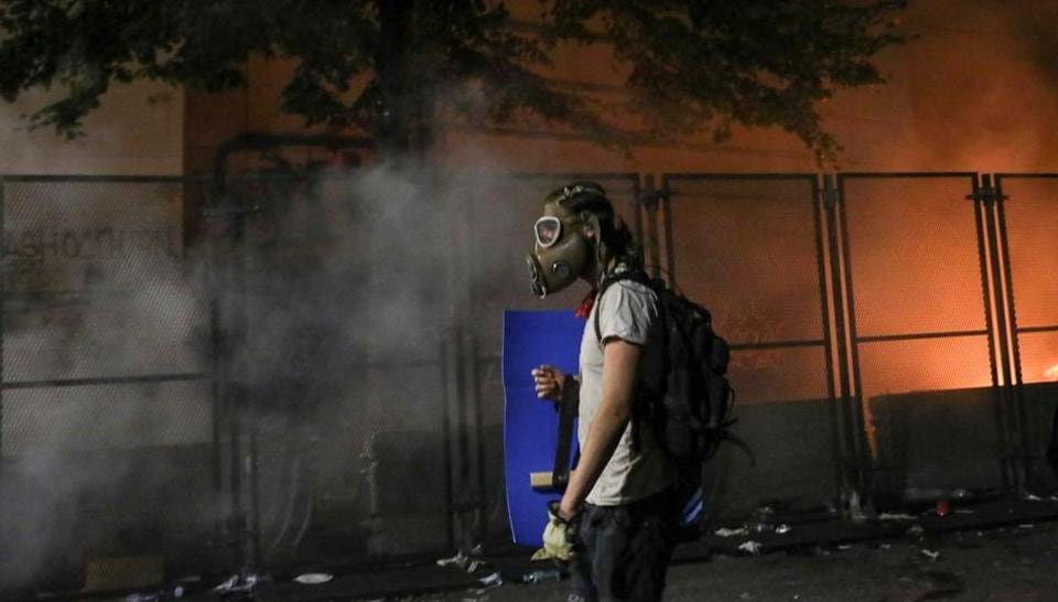 A protester holds a shield and wears a gas mask after federal law enforcement officers fired tear gas outside the Mark O. Hatfield United States Courthouse during a demonstration against the presence of federal law enforcement officers and racial inequality in Portland, Oregon, U.S., July 23, 2020.