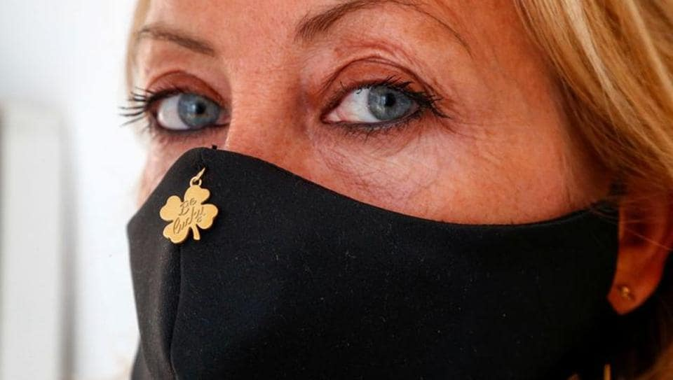 Belgian jewellery designer Olivia Hainaut poses wearing a protective mask with a gold-plated clover reading