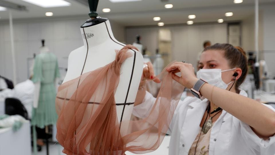 A dressmaker, wearing a protective mask, works ahead of Dior's 2021 Cruise collection presentation by designer Maria Grazia Chiuri at the Dior fashion house workshop.  (REUTERS/Charles Platiau)