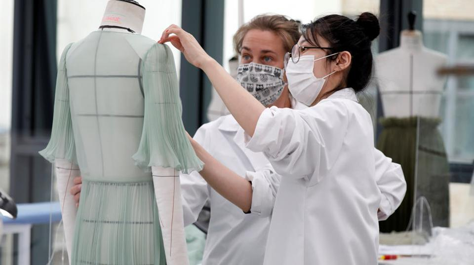 Dressmakers, wearing protective masks, work ahead of Dior's 2021 Cruise collection presentation by designer Maria Grazia Chiuri at the Dior fashion house workshop in Paris.  (REUTERS/Charles Platiau)
