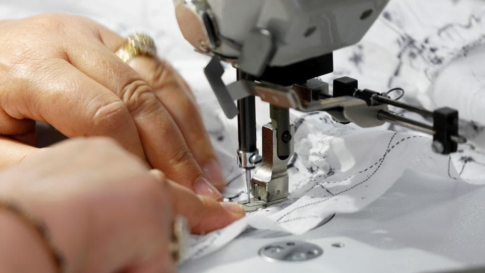 A dressmaker works ahead of Dior's 2021 Cruise collection presentation by designer Maria Grazia Chiuri at the Dior fashion house workshop in Paris, France.  (REUTERS/Charles Platiau)