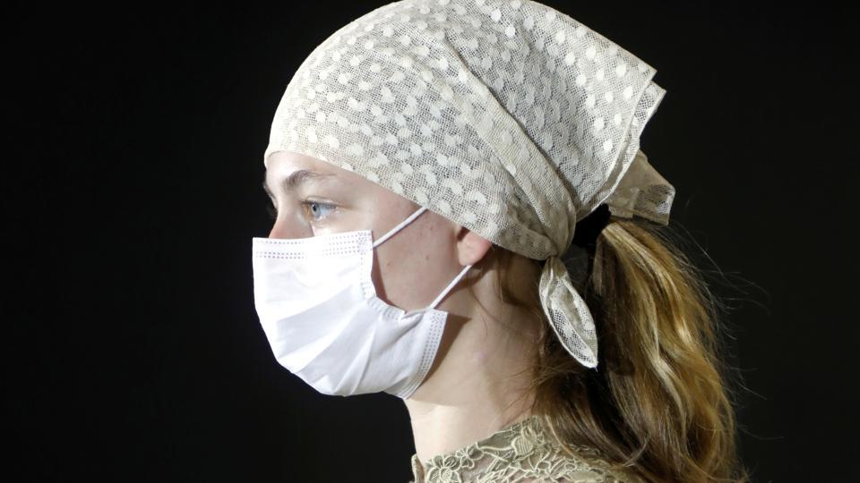 A model, wearing a protective mask, takes part in a fitting ahead of Dior's 2021 Cruise collection presentation by designer Maria Grazia Chiuri at Dior fashion house in Paris, France.  (REUTERS/Charles Platiau)