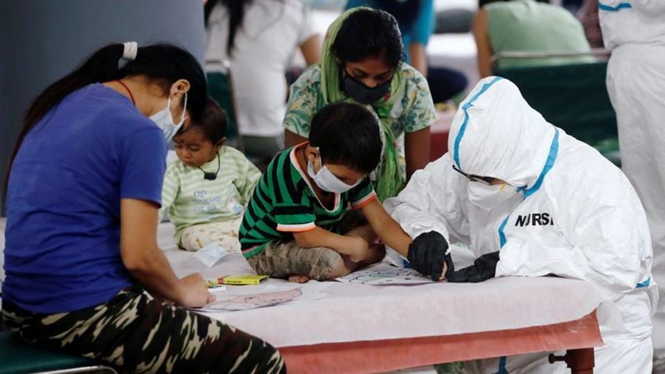 A medical worker helps a boy to draw inside a care centre for the coronavirus disease (Covid-19) patients at an indoor sports complex in New Delhi,on July 20.