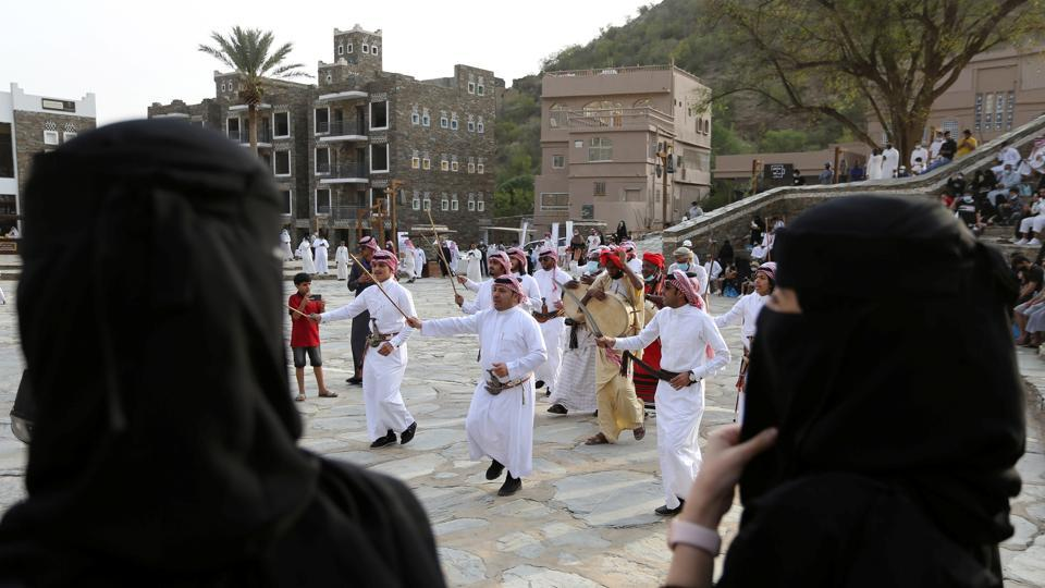 Tourists watch Saudi men perform a traditional folk dance at the cultural village of Rijal Almaa in the outskirts of Abha, Saudi Arabia July 17, 2020. (REUTERS)