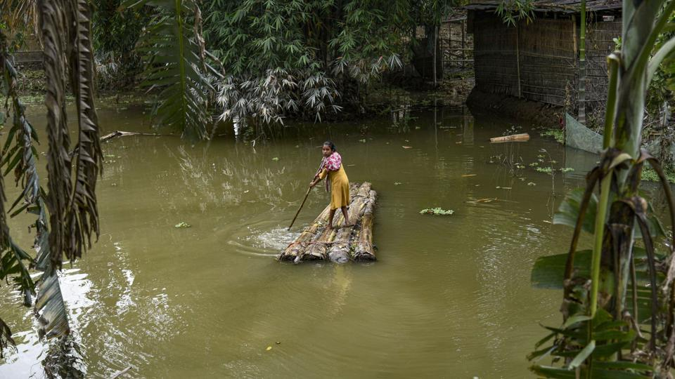 A woman rows a makeshift raft to cross a flood-affected area in Morigaon district of Assam on July 20. According to the flood report by the Assam State Disaster Management Authority (ASDMA), nearly 2,631,343 people have been severely affected by the floods, with Barpeta, Dibrugarh, Kokrajhar, Bongaigaon, Tinsukia being the most affected districts.  (PTI)