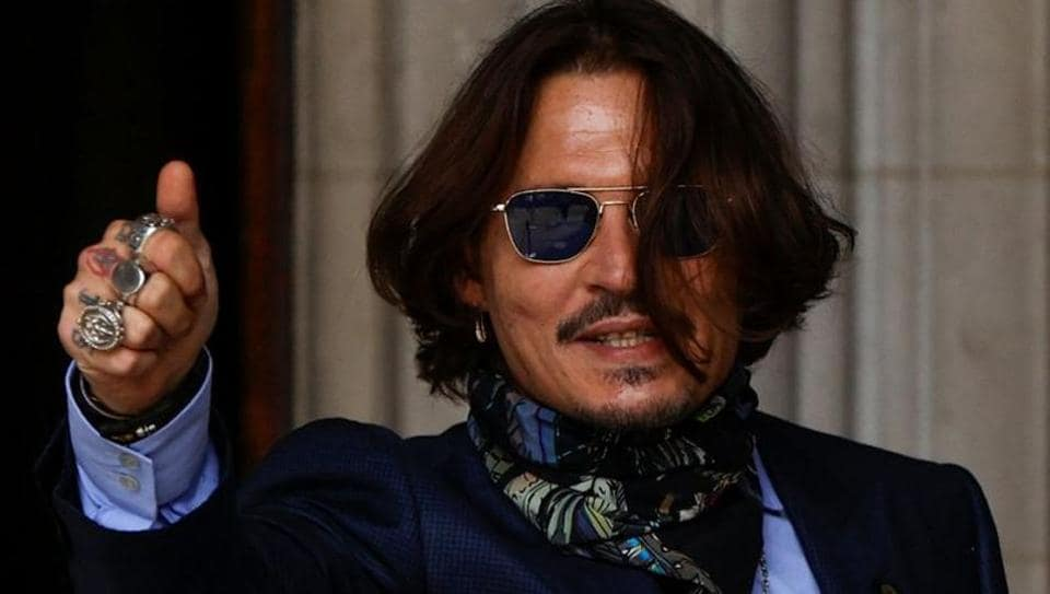 Actor Johnny Depp gestures as he arrives at the High Court in London.
