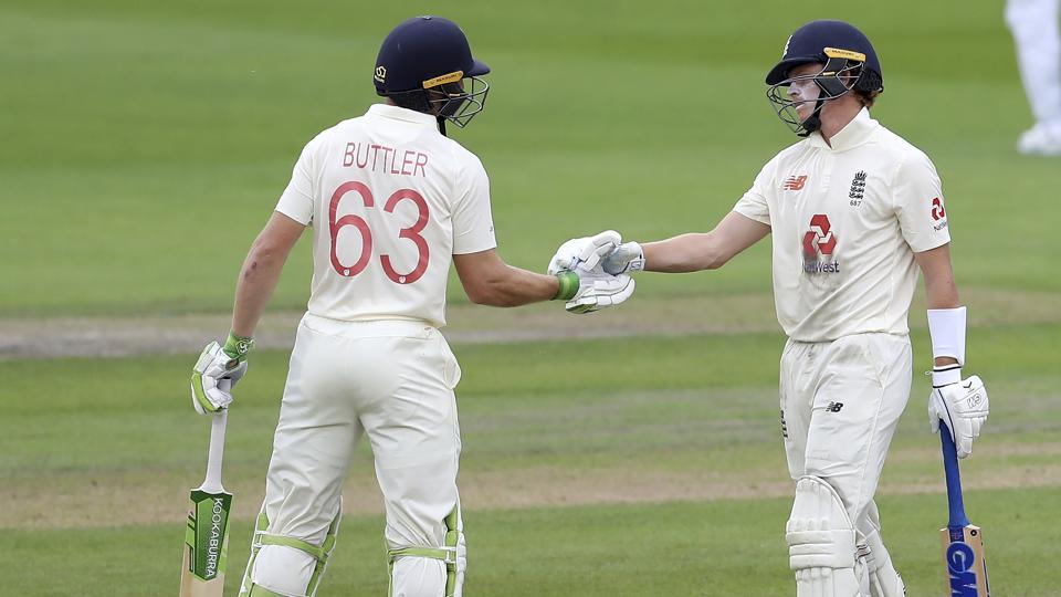 England's Jos Buttler, left, congratulates teammate Ollie Pope on scoring fifty runs during the first day of the third cricket Test match between England and West Indies at Old Trafford in Manchester, England, Friday, July 24, 2020.