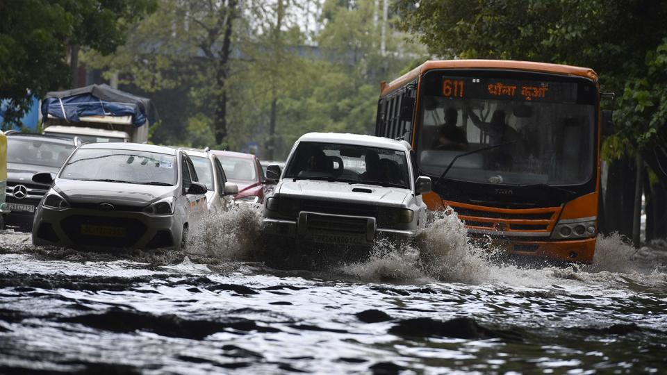 Commuter make way through a water-logged road, at Ring Road, in New Delhi.