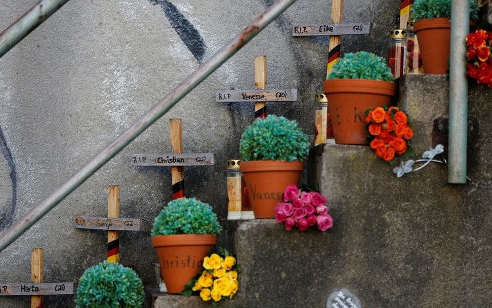 Crosses and flower pots with names of the victims are seen at  a memorial at the