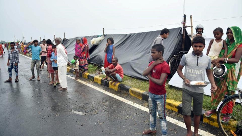 "Flood-affected people take shelter on a highway road while waiting for help in Darbhanga on July 22. ""We will have to stay here till our area remains flooded. We don't have food. No one from the administration has come yet. Everything has submerged and the water levels are increasing constantly."" Nandu Kumar, a local resident told ANI.  (ANI)"