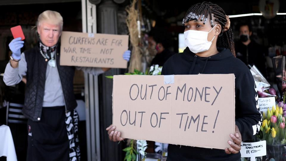A woman holds a placard during a protest by members of the restaurant industry against the coronavirus disease restrictions in Johannesburg on July 22. President Ramaphosa implemented a tough lockdown at the end of March but a surge in poverty and unemployment in a country that already had too much of both spurred the government to partially lift restrictions before the peak of infections. (Siphiwe Sibeko / REUTERS)