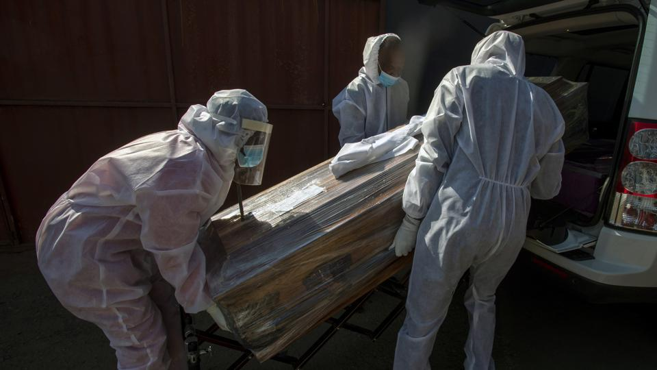 Funeral home workers in protective suits carry the coffin of a woman who died from COVID-19 in Katlehong, on July 21. South Africa, last Saturday became one of the top five worst-hit countries in the coronavirus pandemic, as breathtaking new infection numbers around the world were a reminder that a return to normal life is still far from sight.  (Themba Hadebe / AP)