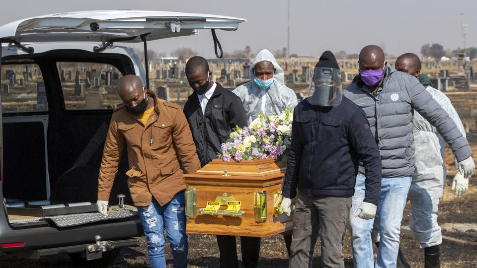 Family members and funeral workers in a protective gear carry the coffin of a COVID-19 victim in Thokoza on July 23. South Africa witnessed 17,000 extra deaths from natural causes or 59% more than would normally be expected between early May and mid-July, scientists said, suggesting many more people are dying of COVID-19 than shown in official figures, Reuters reported.  (Themba Hadebe / AP)