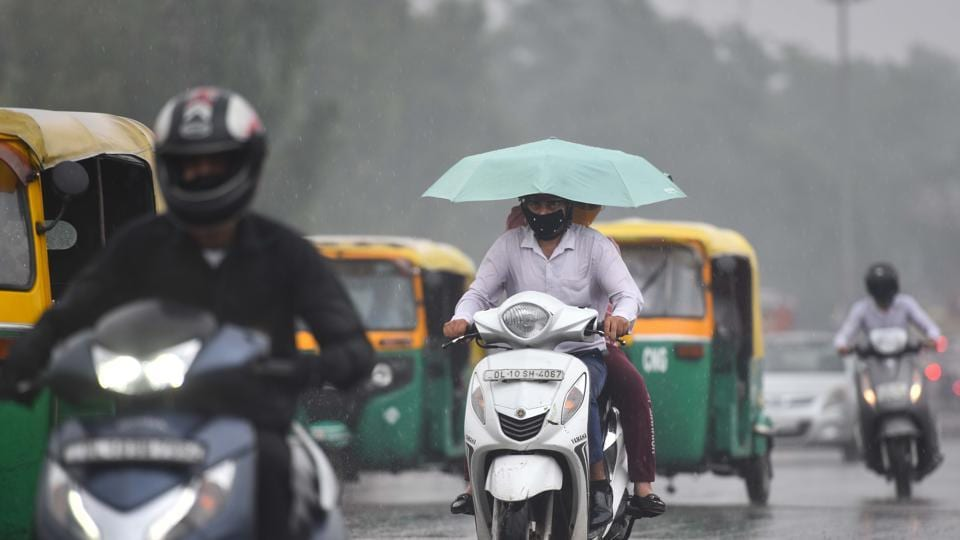 File photo of commuters out in the rain in  New Delhi.