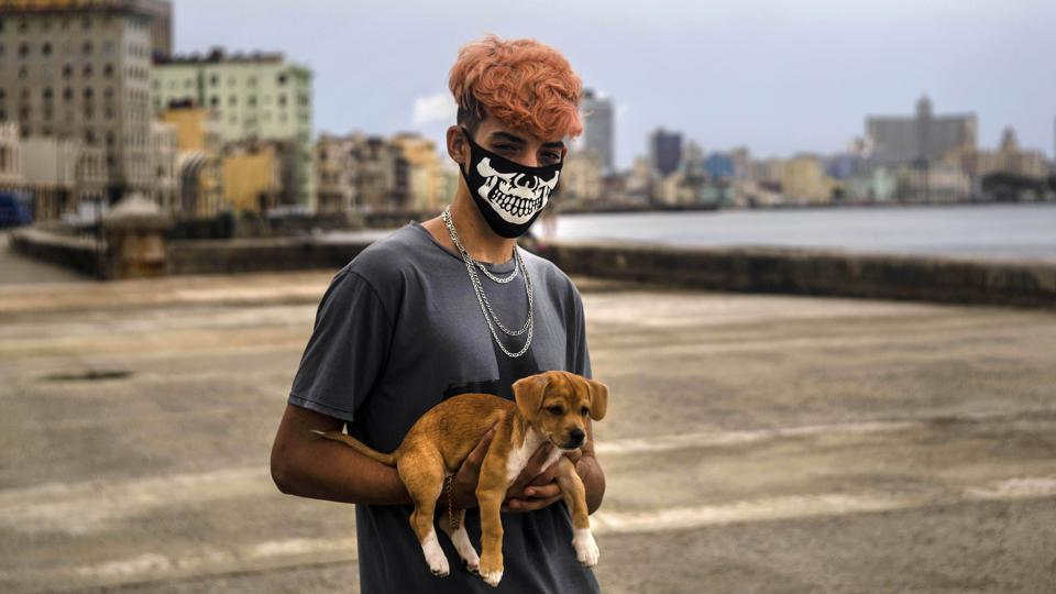 Poo Alejandro Padrun, 15, wearing a protective face masks as a precaution against the spread of the novel coronavirus (Covid-19) poses with his dog in the Malecon esplanade in Havana, Cuba on July 22.