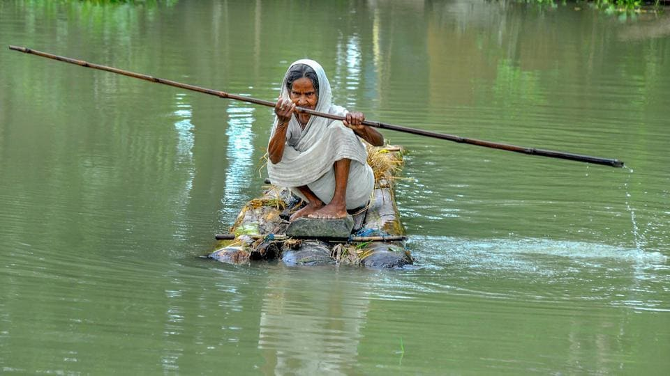 An elderly woman rows a makeshift raft to cross a flood-affected area of Mayong village in Morigaon district of Assam.