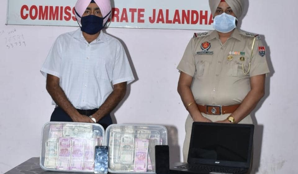 Police officials with the cash seized from a Jalandhar based cricket bookie.