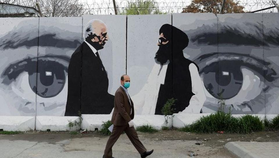 An Afghan man wearing a protective face mask walks past a wall painted with photo of Zalmay Khalilzad, US envoy for peace in Afghanistan, and Mullah Abdul Ghani Baradar, the leader of the Taliban delegation, in Kabul, Afghanistan.