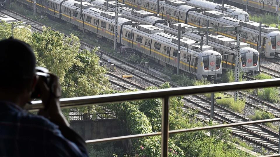 A man photographs Delhi Metro yellow line trains parked at Khyber Pass Metro Depot, in New Delhi.