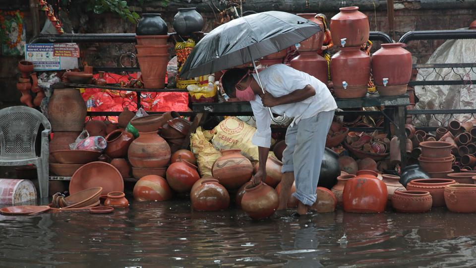 A potter grabs his earthen pitchers from getting swept away during rain on Ajmer road in Jaipur, Rajasthan on Saturday.