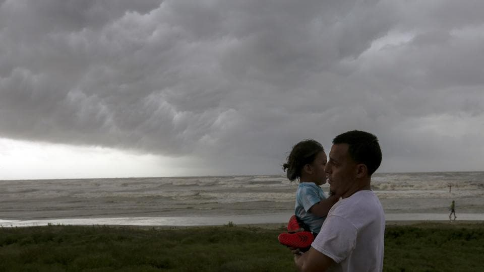 People walk along Seawall Boulevard as a band of heavy rain and wind approaches, in Galveston, Texas