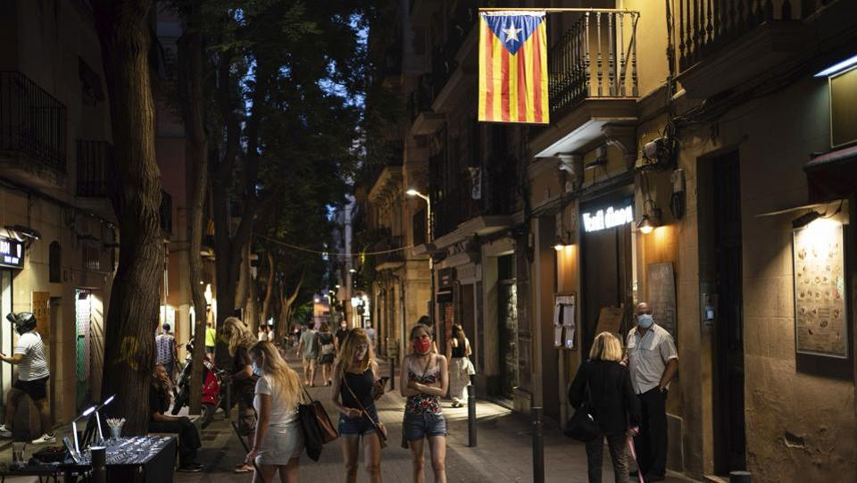People walk at night in Gracia neighborhood in Barcelona on July 24. Catalonia's regional government, run by separatists who had complained about Spain's centralization of the health crisis from March to June, is struggling to maintain tabs on the growing clusters that have overwhelmed undermanned contact tracing teams. (Felipe Dana / AP)